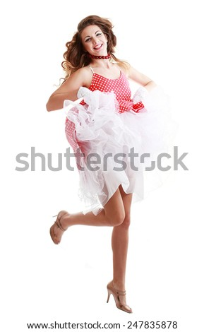 Ecstatic woman dancing and celebrating. Excited happy and joyful caucasian young beautiful woman isolated in full length on white background. Red hair and dress. - stock photo