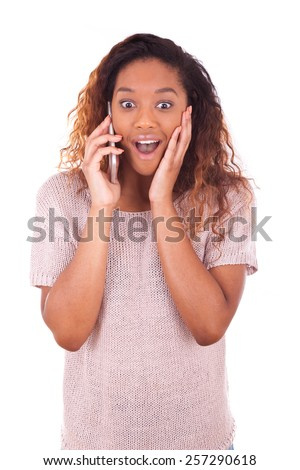 Ecstatic young African American woman making a phone call on her smartphone - stock photo