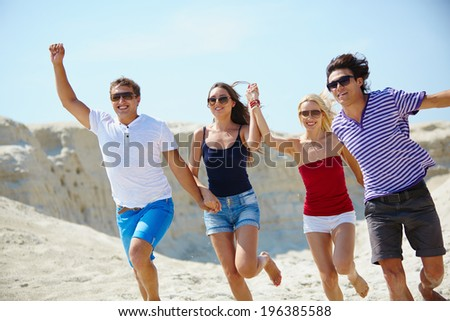Ecstatic young people holding by hands while running down sandy beach - stock photo
