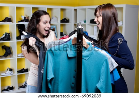 Ecstatic young woman buying clothes with her friend