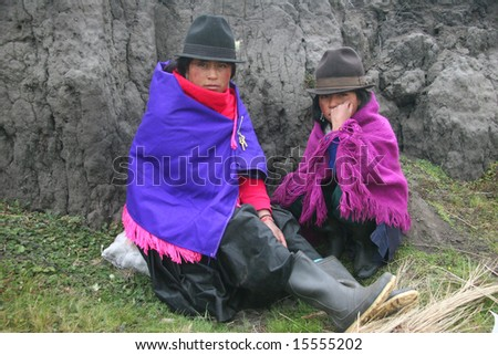 ECUADOR-  SEPTEMBER 02: Two girls covered with traditional clothes posing in front of a rock. Great Trekking adventure September 02, 2005 in Ecuador.