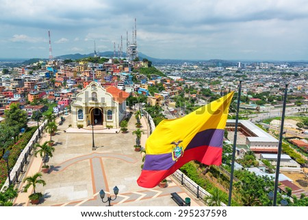 Ecuadorian flag on top of Santa Ana hill with a church and the city of Guayaquil visible in the background in Ecuador - stock photo