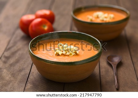Ecuadorian tomato and potato cream soup served with popcorn on top in rustic bowls (Selective Focus, Focus on the front of the popcorn on the soup) - stock photo