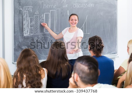 Ecxited positive student gives answer near blackboard during lesson