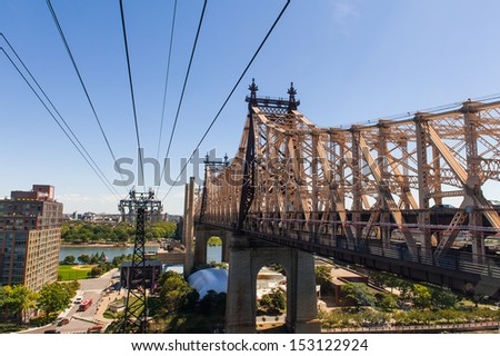 Ed Koch Queensboro Bridge and the Funicular under the blue sky  - stock photo
