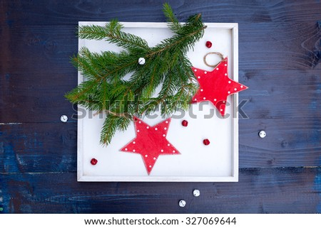 ed wooden stars, pine branch in a white box, red and white bells. christmas decoration