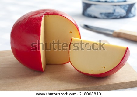 Edam cheese and a piece on a cutting board - stock photo