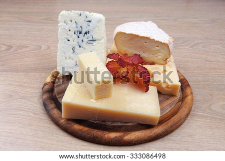 edam parmesan and brie cheese on wooden platter over wooden table - stock photo