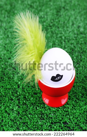 Edd in egg cup on green background - stock photo
