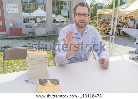EDEN MILLS, ON - SEPTEMBER 16:  Canadian writer, Andrew Westoll, signs copies of  one of his recent books at the annual Writers Festival in Eden Mills, Ontario on September 16, 2012. - stock photo