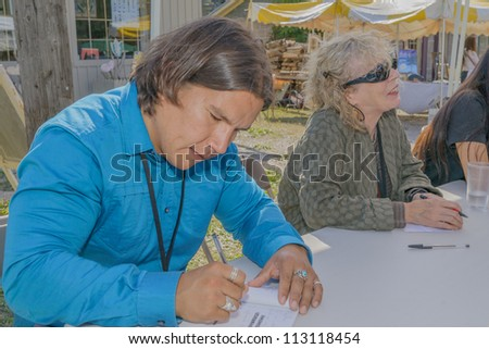 EDEN MILLS, ON - SEPTEMBER 16:  Prize winning Canadian writers Waubgeshig Rice and Eva Stachniak sign their books at the annual Writers Festival in Eden Mills, Ontario on September 16, 2012. - stock photo