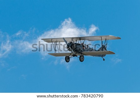 EDEN PRAIRIE, MN - JULY 16 2016: 1929 Curtis-Wright Travel Air E-4000 biplane flies in at airshow. This biplane is flown by a MN based company for historic flight experiences by passengers.