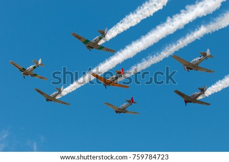 EDEN PRAIRIE, MN - JULY 16, 2016: Seven AT-6 Texan planes fly over trailing smoke at air show. The AT-6 Texan was primarily used as trainer aircraft during and after World War II.