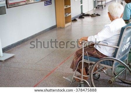 Ederly patient woman at Out Patient Department on wheelchair in hospital, Feeling of waiting, warm filter - stock photo