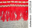 Edge of a bright red kilim rug on the floor - stock photo