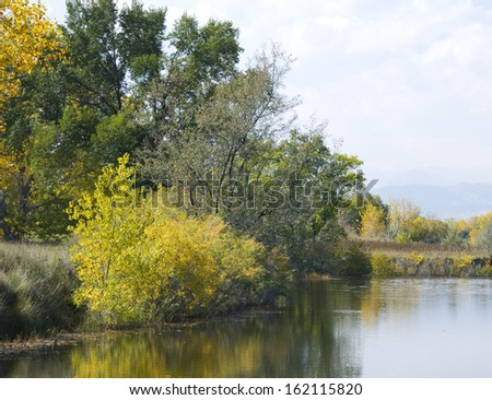 Edge of a full pond in a wetlands area on the Colorado prairie in autumn with autumn foliage - stock photo