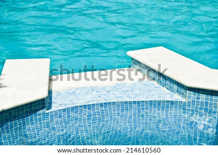 Edge of swimming pool with blue tiles - stock photo