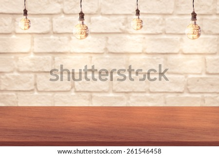 edge of wood table and white brick wall background with light bulbs - stock photo