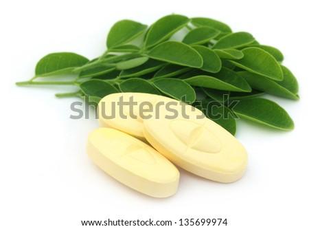 Edible moringa leaves with pills - stock photo