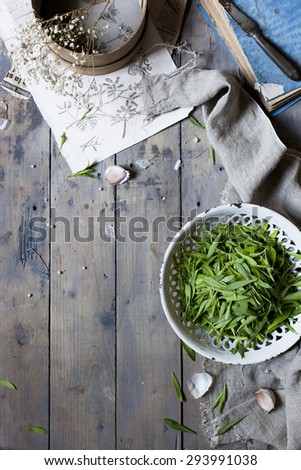 edible seasonal wild herbs on plate on a rustic kitchen table - stock photo