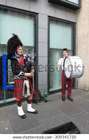 EDINBUGH, SCOTLAND, UK - CIRCA AUGUST 2015: Scottish bagpiper and drummer dressed in traditional red and black tartan dress - stock photo