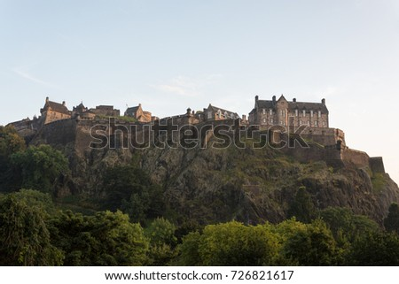 Edinburgh castle during sunset catching the last light surrounded by trees