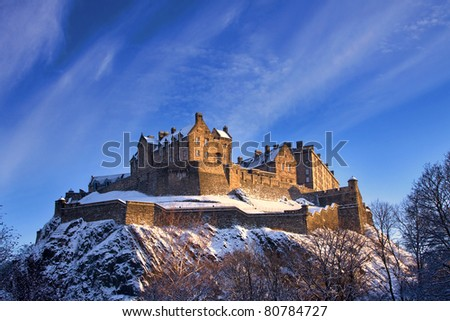 Edinburgh castle dusted with snow glows in the late afternoon winter sunset. - stock photo