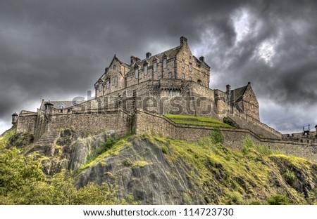 Edinburgh Castle on Castle Rock in Edinburgh, Scotland, UK against dark rainclouds - stock photo