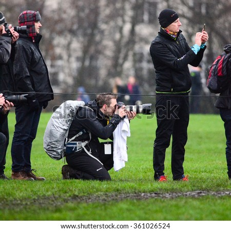 EDINBURGH - JANUARY 9: a photographer at the Great Edinburgh Cross Country event on January 9, 2016 in Edinburgh, Scotland. Edinburgh hosts the athletics event annually in January. - stock photo
