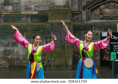 "EDINBURGH,SCOTLAND - August 19: South Korean women dressed in tradition costume, ""Hanbok"", perform a show at Royal Mile street during the Edinburgh Festival Fringe."