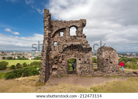 EDINBURGH, SCOTLAND: AUGUST 4, 2014: Tourists at the ruins of St Anthony's Chapel in Holyrood Park. Park's highest point Arthur's seat is popular destination for hiking and enjoying nature.  - stock photo