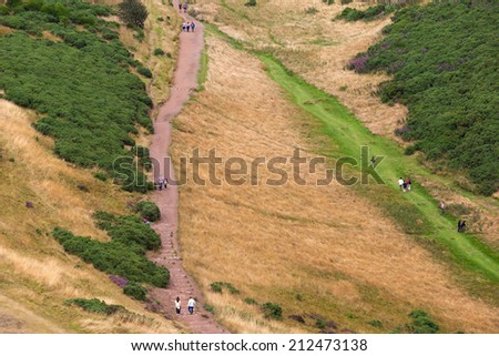 EDINBURGH, SCOTLAND: AUGUST 4, 2014: Tourists walking on path in Holyrood Park. Park's highest point Arthur's seat is popular destination for hiking and enjoying nature.  - stock photo