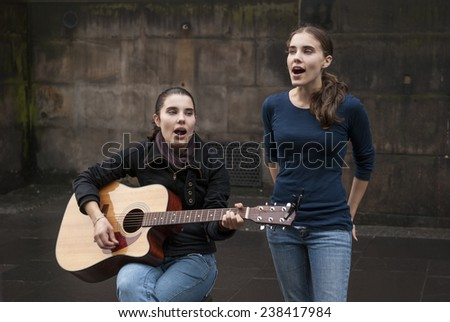 EDINBURGH, SCOTLAND - August 19: Twin women singers perform their show on the Royal Mile  street during the Edinburgh Festival Fringe - stock photo