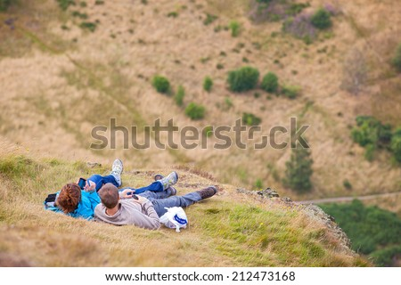 EDINBURGH, SCOTLAND: AUGUST 4, 2014: Young couple laying on grass and enjoying the view from the Arthur's seat in Holyrood Park. Arthur's seat is popular destination for hiking and enjoying nature.  - stock photo