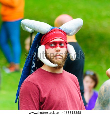 EDINBURGH, SCOTLAND - JULY 17, 2016: Closeup of a male performer wearing a headdress with horns in the Carnival of The Edinburgh Jazz & Blues Festival travelling down the Mound towards Princes Street
