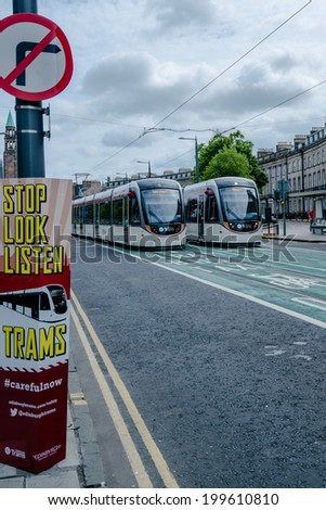 EDINBURGH, SCOTLAND - June 1, 2014: Signs alerting the public to watch out for trams on June 1, 2014 in Edinburgh, Scotland. The city launched its tram public transport system the day before and since - stock photo