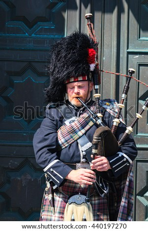 EDINBURGH, SCOTLAND - MAY 29, 2016: A Scotsman wearing traditional Scottish outfit playing the bagpipes along the Royal Mile in Edinburgh, on 29th March 2016.