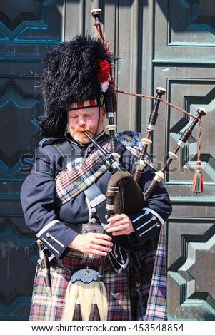 EDINBURGH, SCOTLAND - MAY 29, 2016: A Scotsman wearing traditional Scottish outfit playing the bagpipes along the Royal Mile in Edinburgh, on 29th March 2016. - stock photo