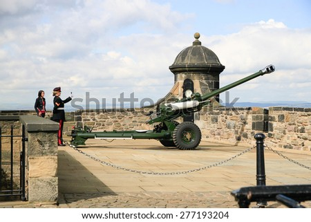 Edinburgh Scotland - September 9 2010 - The honor guard fires the famous Edinburgh cannon which shoots at one o'clock for correct time keeping at the castle - stock photo