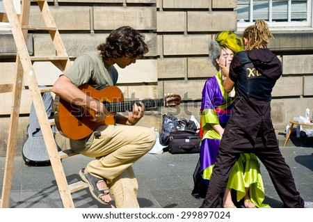 EDINBURGH, SCOTLAND, UK - AUGUST 20 2005. Man put make up on actress  and other man plays guitar on Royal mile during Edinburgh Festival days