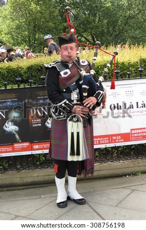 EDINBURGH, SCOTLAND, UK - CIRCA AUGUST 2015: Scottish bagpiper dressed in traditional red and black tartan dress - stock photo