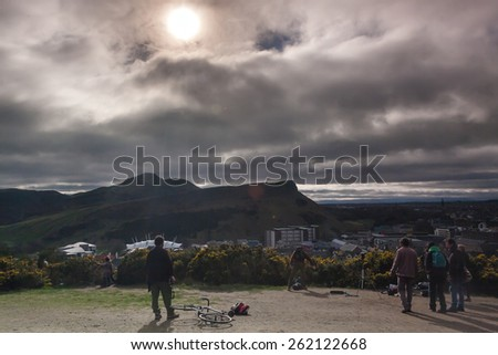 EDINBURGH-SCOTLAND, UK- MARCH 20 : Crowd gathered on Calton hill to witness unique phenomenon of the sun eclipse event on March 20, 2015.  - stock photo