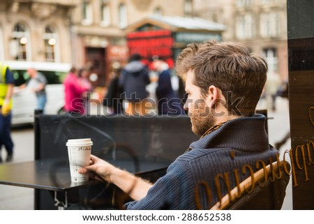 EDINBURGH, SCOTLAND / UNITED KINGDOM - MAY 24 2015 - Unidentified man sitting outside a cafe, watching the people of Edinburgh pass through. - stock photo