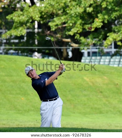 EDISON,NJ-AUGUST 26: Golfer Ernie Els takes a shot out of the rough during the second round of the Barclays Tournament held at the Plainfield Country Club on August 26, 2011 in Edison, N.J. - stock photo