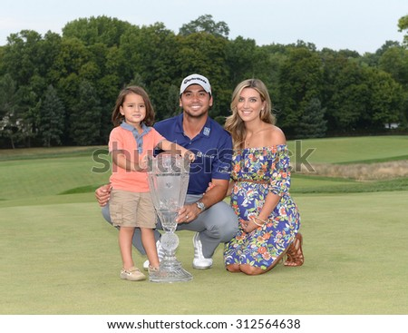 EDISON,NJ-AUGUST 30:Jason Day with his 3 year old son Dash James and his wife Ellie on the 18th green with the Barclays winner's trophy at the Plainfield Countruy Club in Edison,NJ,August 30,2015.  - stock photo