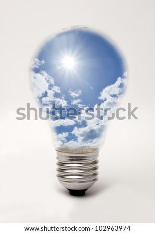Edison screw lightbulb containing sun and blue sky, suggesting solar energy - stock photo