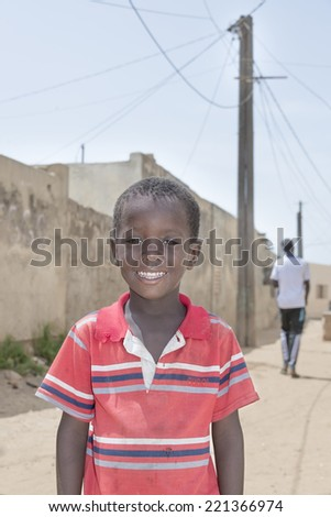 Editorial caption: THIAROYE, SENEGAL, AFRICA  JULY 30, 2014 Unidentified boy standing in the street, popular district of Guinaw Rails - stock photo