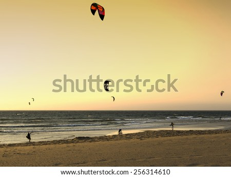 Editorial image. Portugal, Paraia do Guincho, 12.06.2014. Kitesurfing on the beach at sunset. Summer sports - stock photo