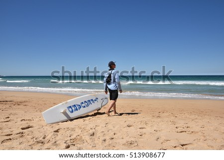 EDITORIAL: NOV 02nd, 2016: Sydney, Australia: Lifeguard and his Surf Board  at famous Manly Beach in Sydney, Australia