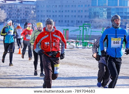 Editorial. Omsk,Russia - January, 07 2018. Leading runners during Urban Christmas winter half marathon in Naberezhnaya Tukhachevskogo street